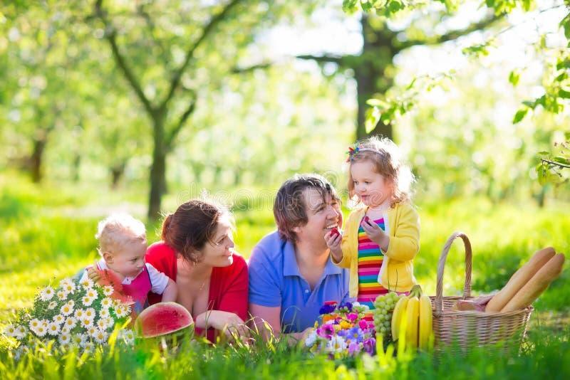 Familj som tycker om picknicken i blommande trädgård arkivfoto