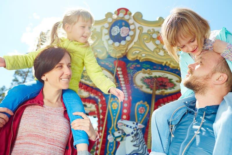 Familj som tycker om solig dag i funfair arkivbilder