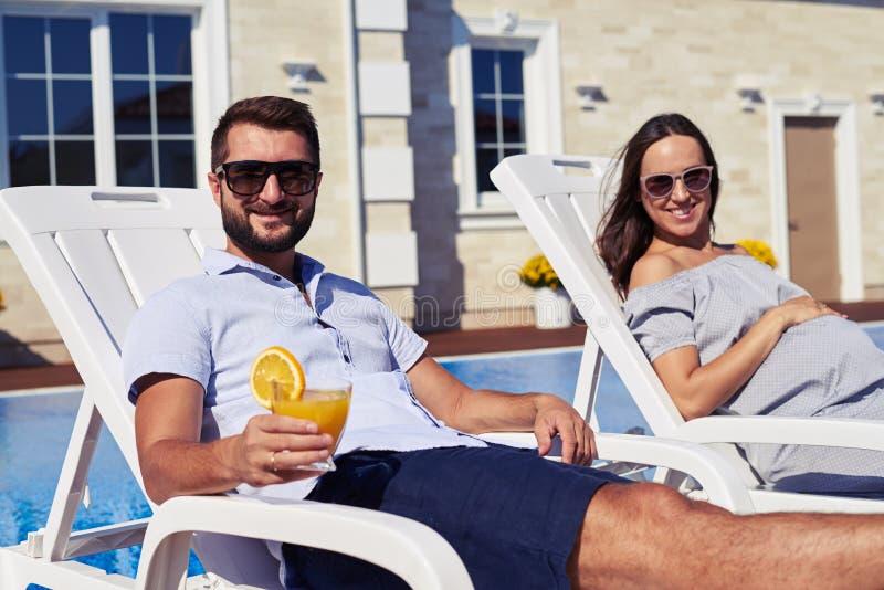 Familj som tycker om solig dag i modern uppehåll nära simbassäng royaltyfria foton