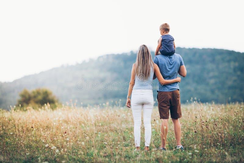 Familj som tycker om tid som tillsammans utomhus spenderas arkivfoto
