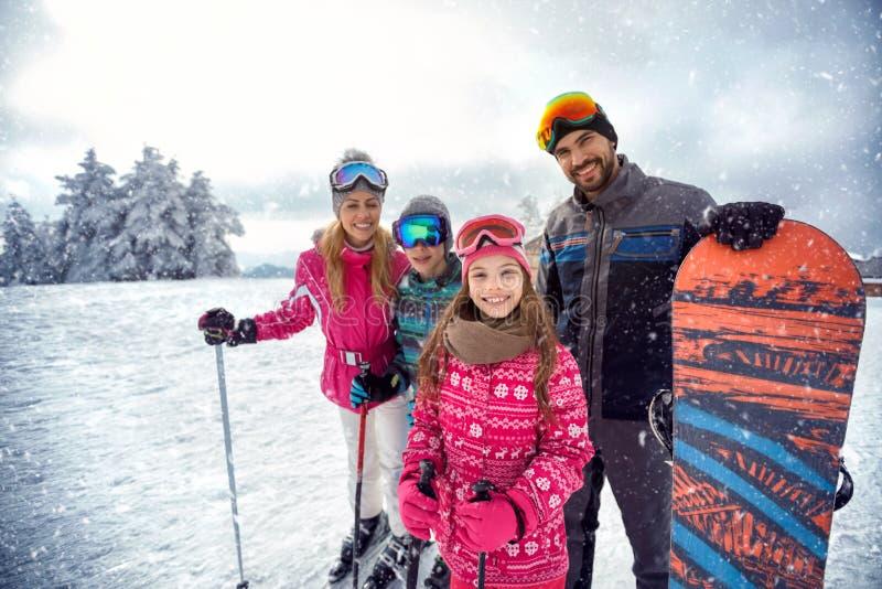 Familj som tycker om vintersportar och semester på insnöade berg royaltyfria foton