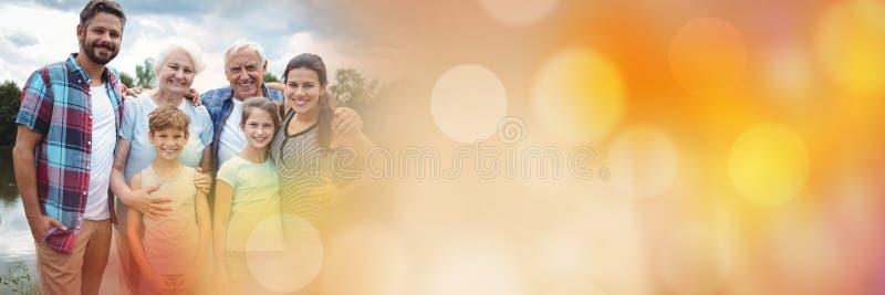 Familj som utanför ler med orange bokehövergång fotografering för bildbyråer