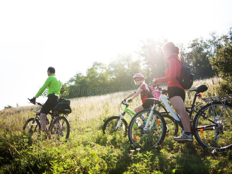 Familj som utomhus cyklar fotografering för bildbyråer