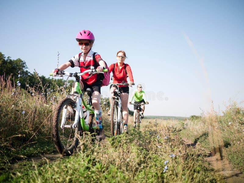 Familj som utomhus cyklar royaltyfria foton