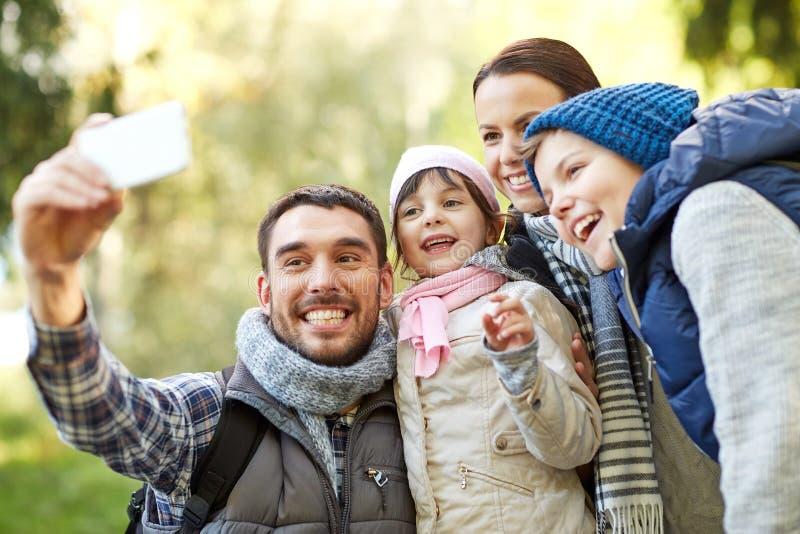 Familj som utomhus tar selfie med smartphonen royaltyfria bilder