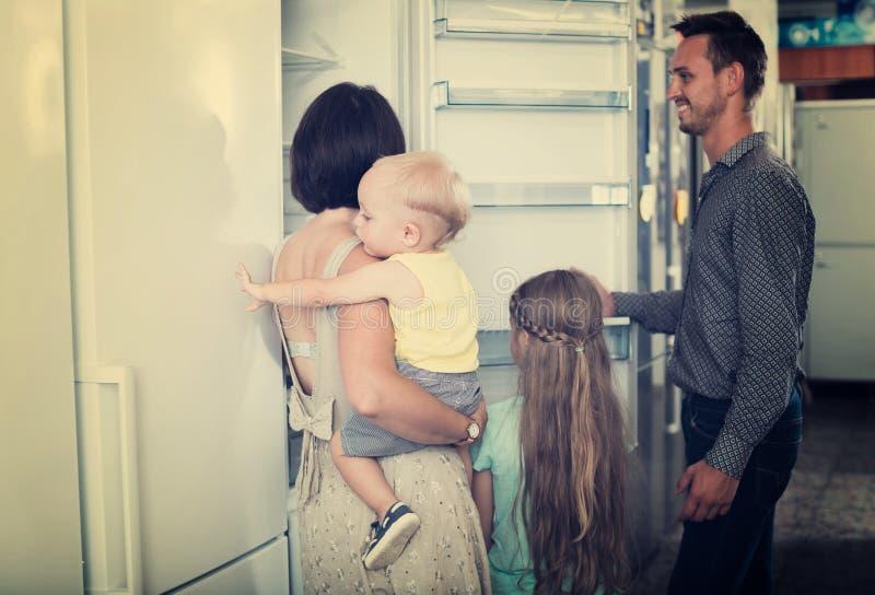 Familj som väljer den nya frysen i lager royaltyfri bild