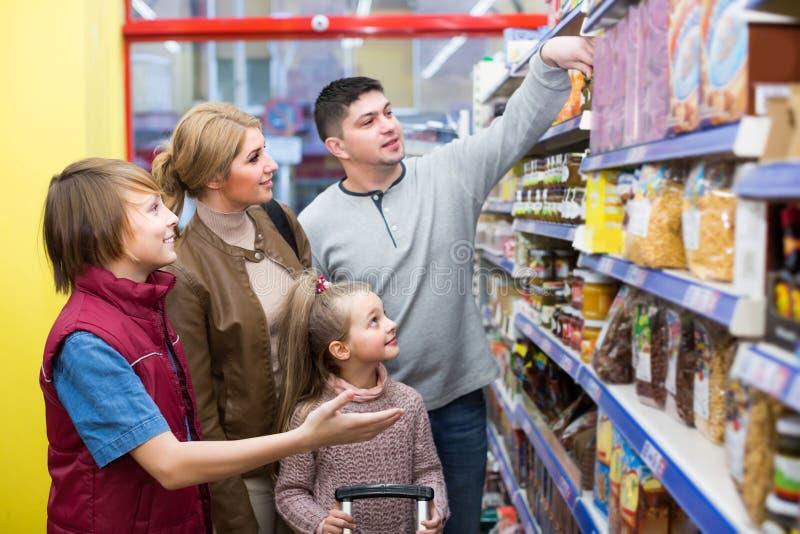 Familj som väljer sädesslag i supermarket arkivfoton