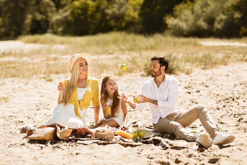 Familj som vilar i natur och att ha picknicken på filten fotografering för bildbyråer