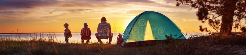 Familj som vilar med tältet i natur på solnedgången royaltyfria bilder