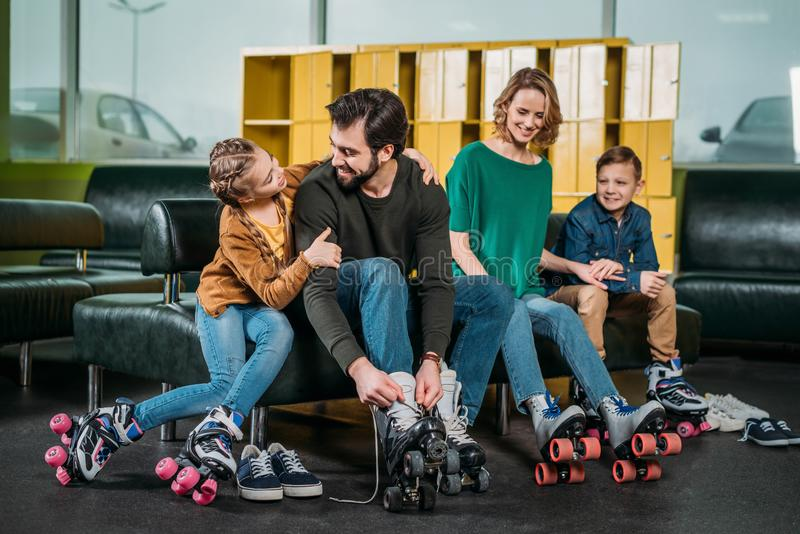 familj som vilar på soffan, innan att åka skridskor i rullskridskor royaltyfri fotografi