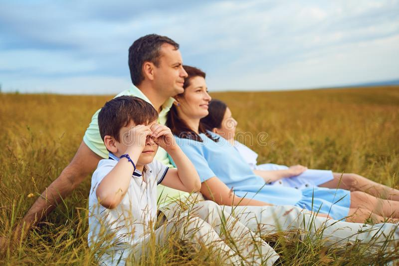 Familj som vilar tillsammans att sitta på gräs i natur royaltyfri bild