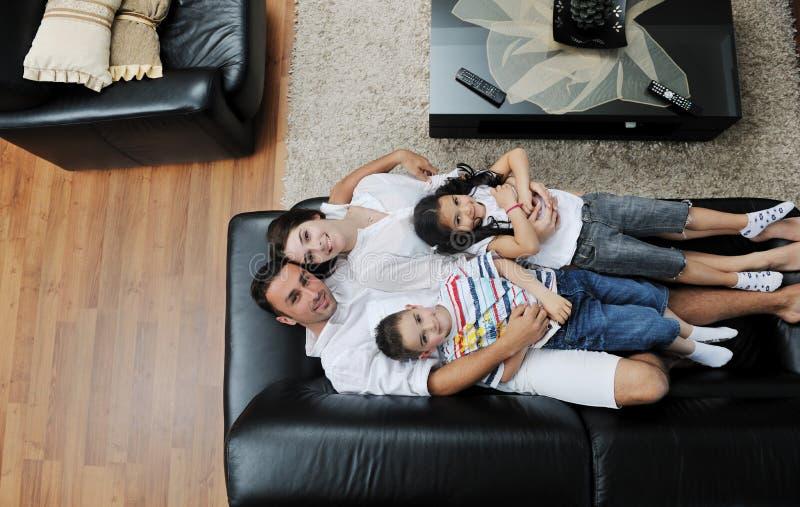 Familj som wathching den plana tv:n på modernt home inomhus arkivfoto