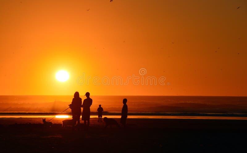 Familj under solnedgång på den Oregon kusten arkivbilder
