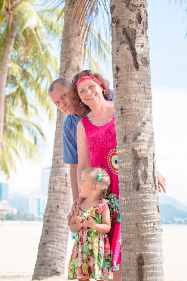 Familj utveckling - den lyckliga le farmodern, farfadern och den lilla ställningen nära gömma i handflatan på stranden arkivbild