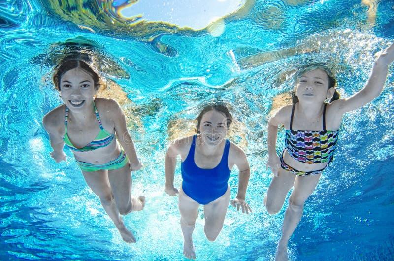 Familjbad i undervattens- lycklig aktiv moder för pöl och barn har gyckel under vatten, kondition och sport med ungar royaltyfri foto