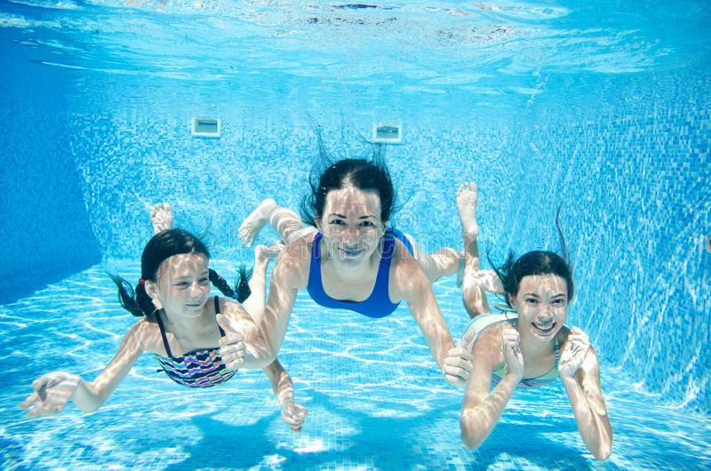 Familjbad i undervattens- lycklig aktiv moder för pöl och barn har gyckel under vatten, kondition och sport med ungar arkivbild
