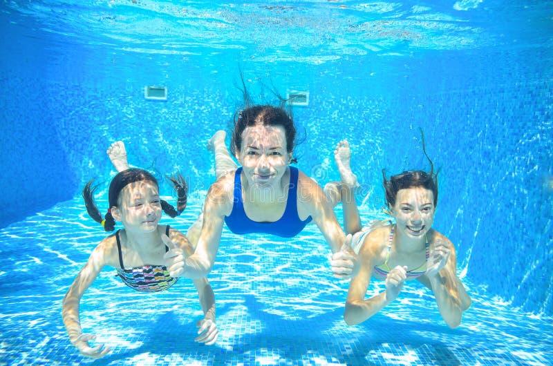 Familjbadet i undervattens- lycklig aktiv moder för pöl och barn har gyckel i vatten, ungesport arkivfoto