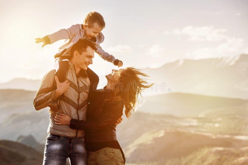 Familjbarn som går bergsolnedgång arkivbild