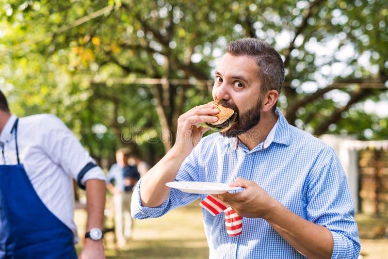 Familjberöm eller ett grillfestparti utanför i trädgården royaltyfri fotografi
