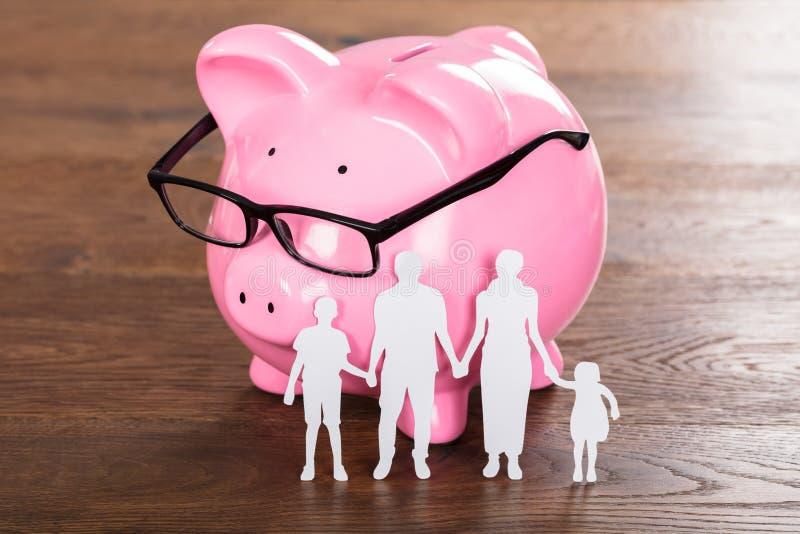 Familjbesparingbegrepp på träskrivbordet arkivbilder