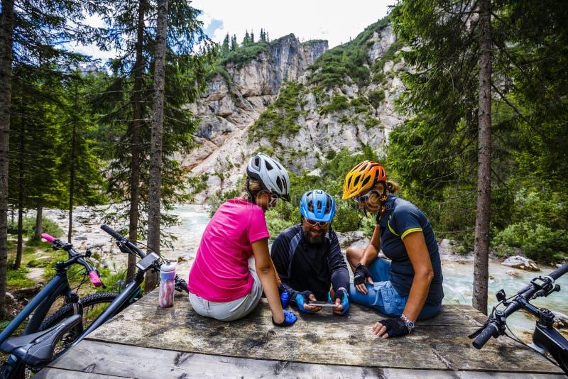Familjcykeln rider i bergen, medan koppla av på bänken c arkivfoton