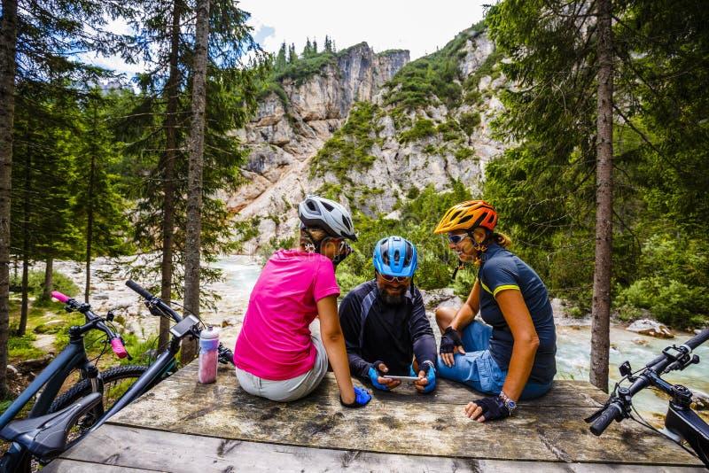 Familjcykeln rider i bergen, medan koppla av på bänken c arkivbilder