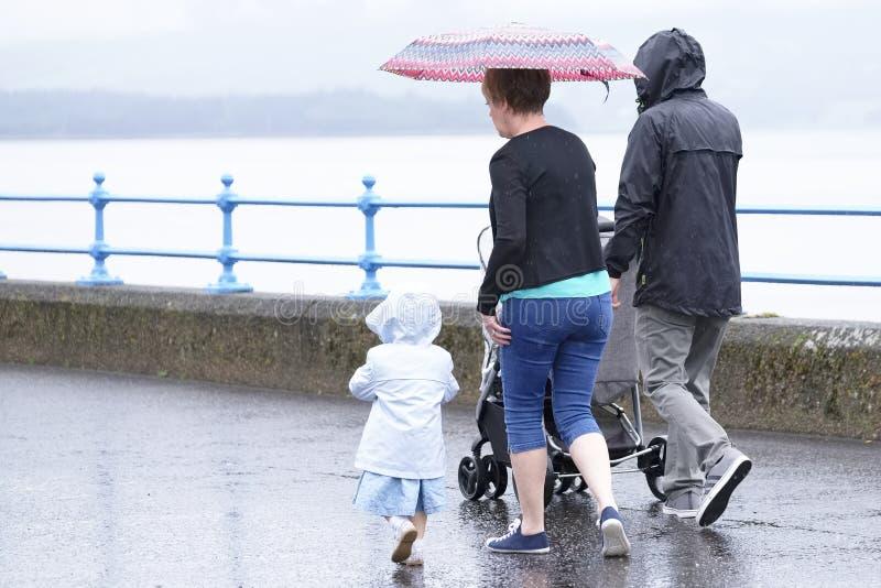 Familjdag ut med sommar för vått väder för paraply brittisk arkivbild