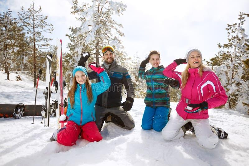 Familjdanandesnö klumpa ihop sig på skidåkning i berg arkivbild