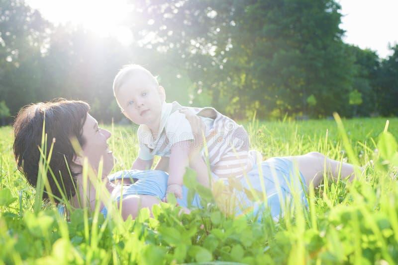 Familjelivbegrepp Stående av modern med hennes spela för litet barnson som är utomhus- royaltyfri bild
