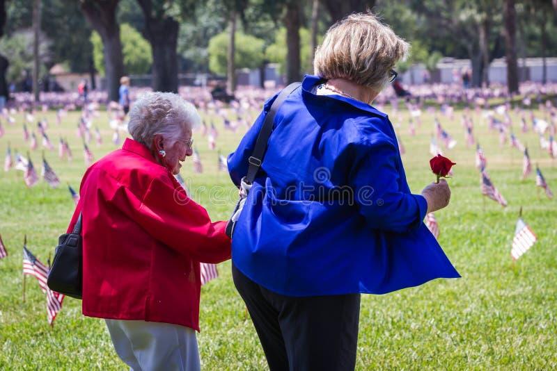 Familjemedlemmar som besöker kyrkogården på minnesdagen arkivfoton