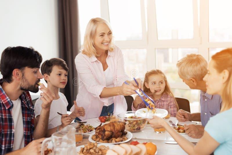 Familjen äter på den festliga tabellen för tacksägelse En kvinna lägger ut mat, hennes familj äter redan royaltyfri bild