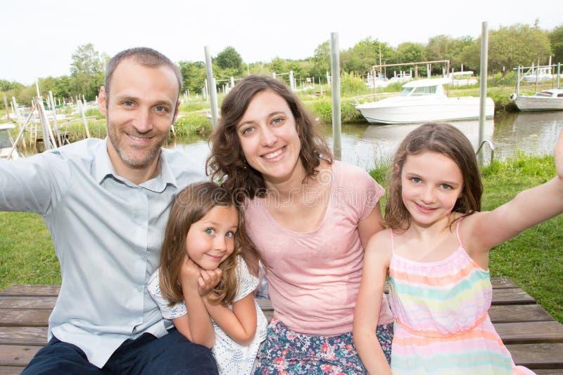 Familjen av fyra gör selfie den utomhus- fadern att fostra och dottersystern royaltyfria foton