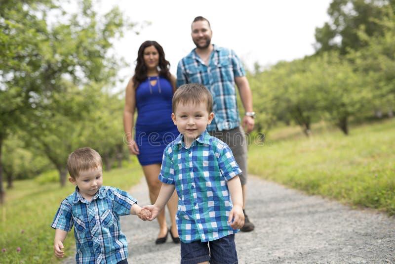 Familjen av fyra har gyckel i skogen royaltyfria bilder