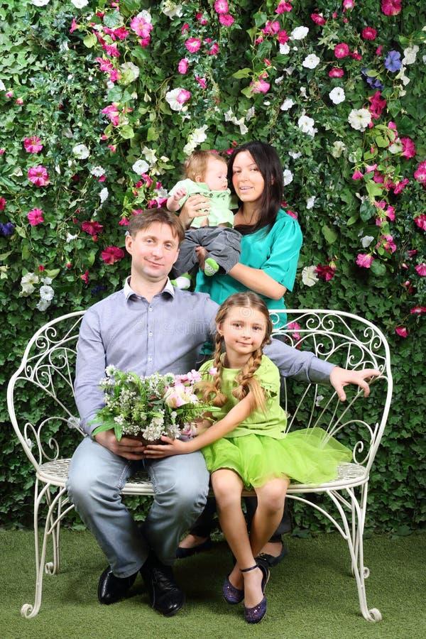 Familjen av fyra sitter på den vita bänken med gruppen av blommor arkivfoto