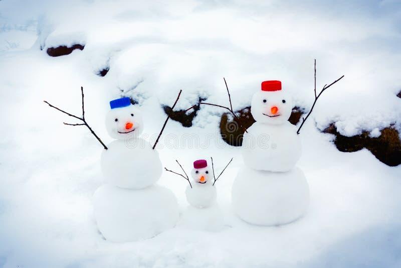 Familjen av gladlynta sn?gubbear jublar p? ankomsten av vintern och den f?rsta sn?n arkivbilder