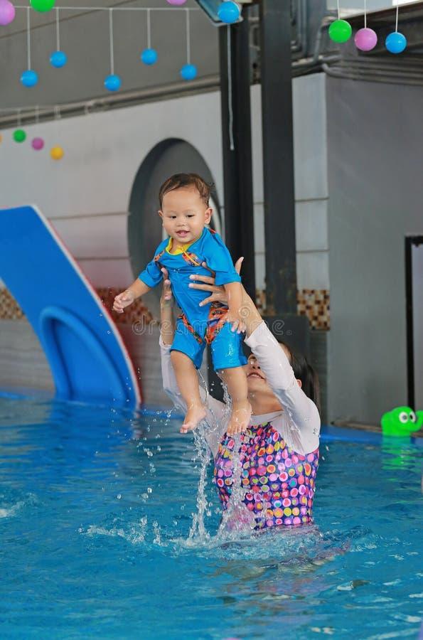 Familjen av moderundervisning behandla som ett barn i simbassäng royaltyfri foto