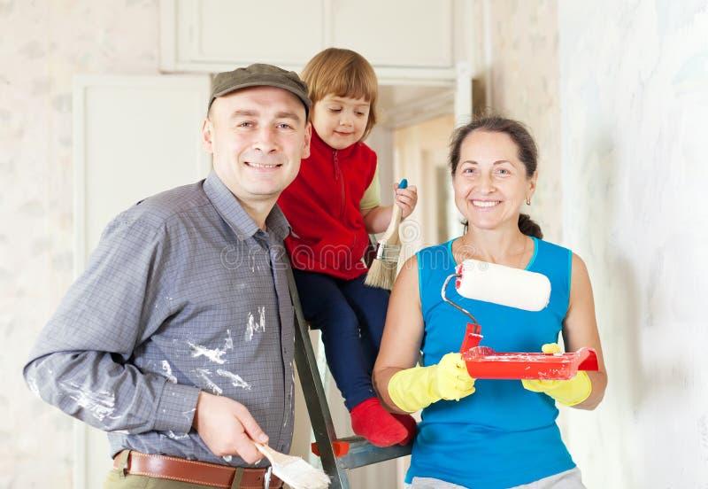 Familjen av tre gör reparationer hemmastadda royaltyfri foto