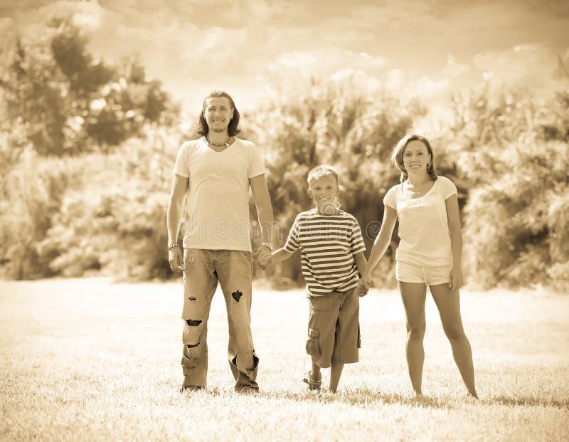Familjen av tre i soligt parkerar arkivbilder