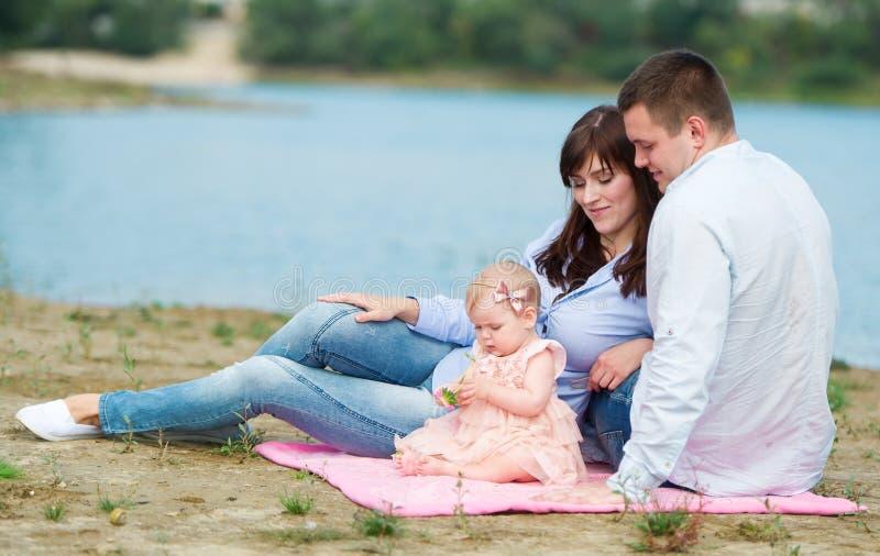 Familjen av tre personer har en vila utomhus royaltyfri bild