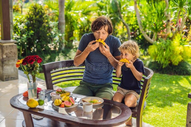 Familjen av två som utmärkt äter, tjänade som frukosten utanför den stiliga unga mannen som häller något kaffe och hans gulliga ä fotografering för bildbyråer