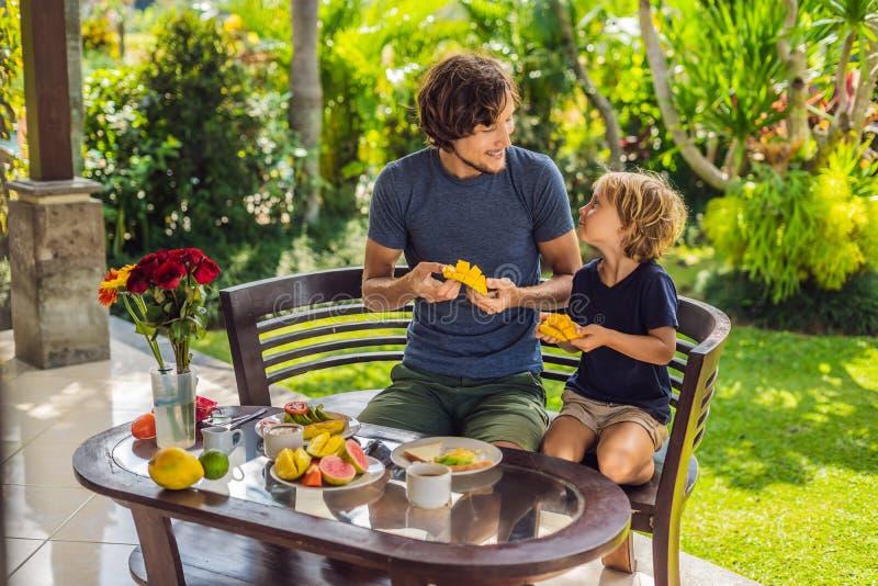 Familjen av två som utmärkt äter, tjänade som frukosten utanför den stiliga unga mannen som häller något kaffe och hans gulliga ä arkivfoton