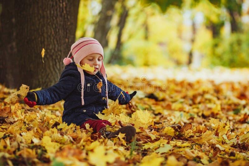 Familjen, barndom, nedgångsäsongen och folkbegreppet, den lyckliga flickan som spelar med höstsidor parkerar in det lilla barnet, arkivbilder
