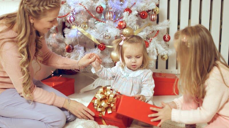 Familjen består av kvinnlina som sitter runt om julgranen med gåvor royaltyfri fotografi
