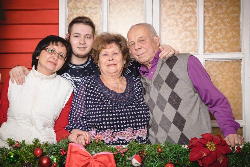 Familjen består modern, farmodern, farfadern, sonson i rummet som dekoreras för jul arkivbild
