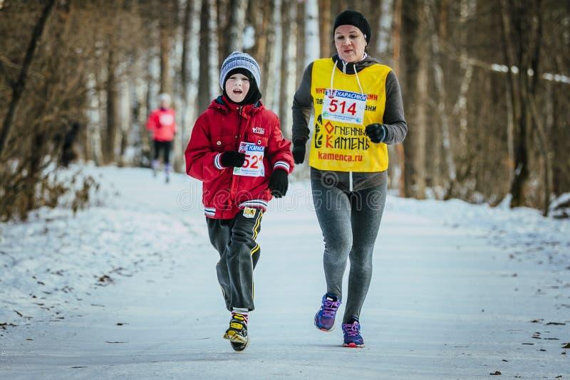 Familjen, en son och modern kör tillsammans vinterträn arkivfoto
