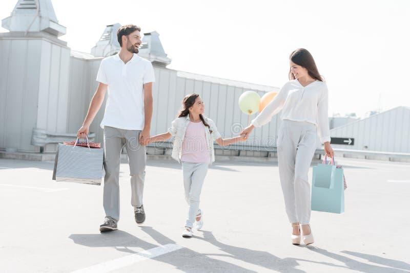 Familjen, fadern, modern och dottern går på vägen nära parkering, når de har shoppat i galleria fotografering för bildbyråer