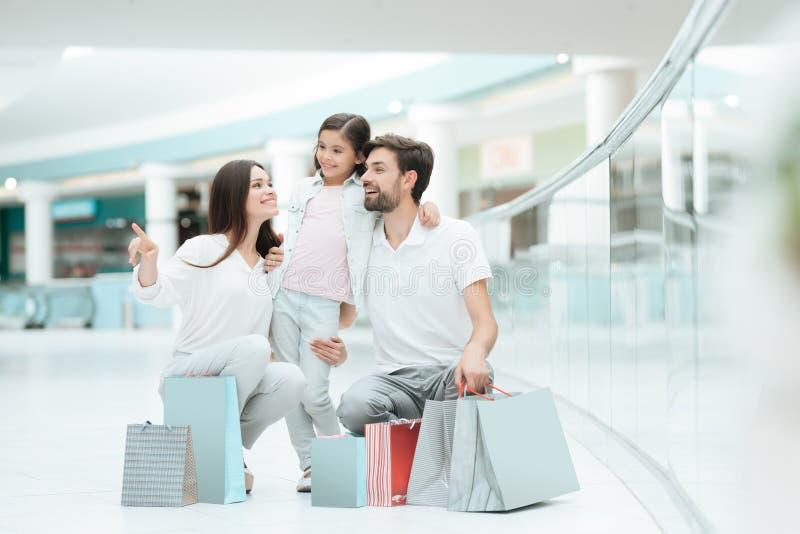 Familjen, fadern, modern och dottern sitter i shoppinggalleria royaltyfri foto