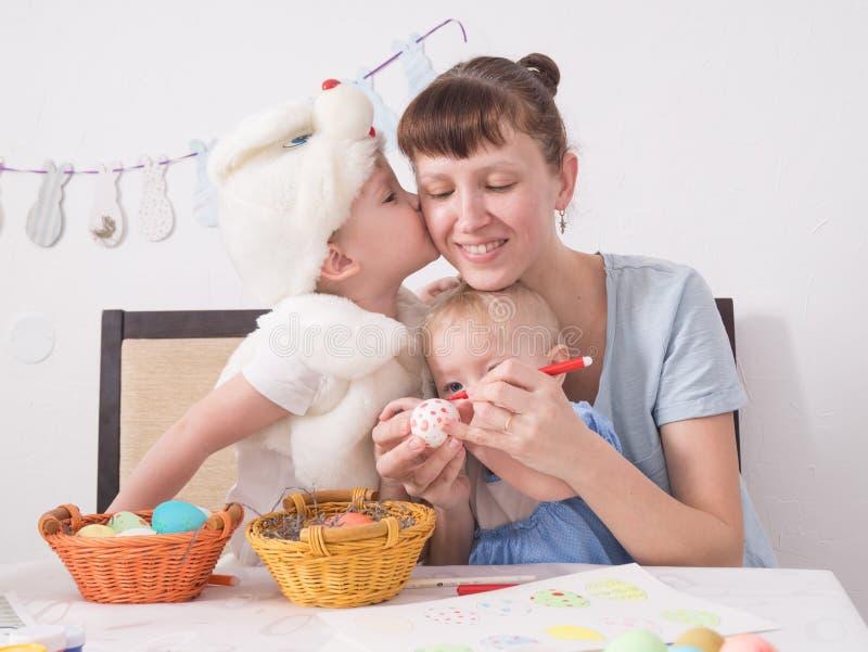 Familjen firar påskhögtiden: Mamman målar en modell på påskägget Sonen kysser hans moder på kinden arkivfoton