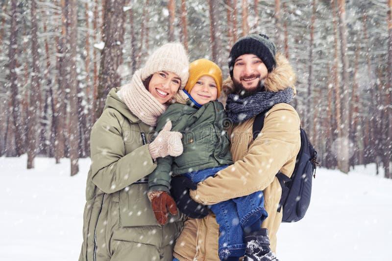 Familjen går av Caucasian par som ler och rymmer sonen på händer fotografering för bildbyråer