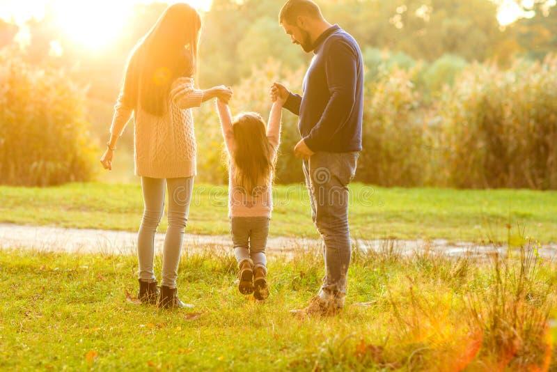 Familjen går i parkera som är lycklig på solnedgången arkivbilder